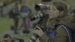 Girl photographer working during the match Footage