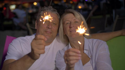 Senior couple with Bengal lights outdoor at night Footage