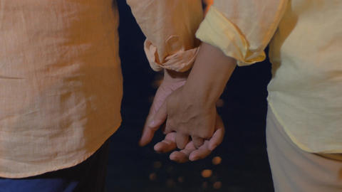 Senior couple holding hands by the sea at night Footage