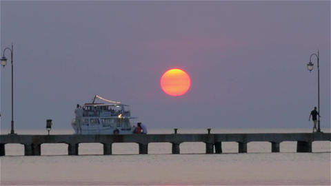 Ferry sailing by the pier with people at sunset Footage