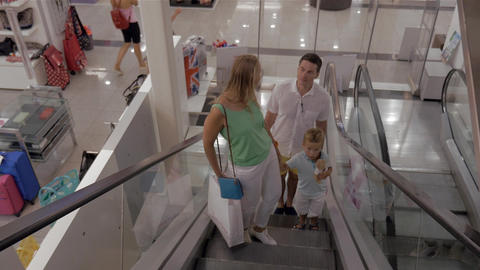 Young family with child riding escalator in shopping center Footage
