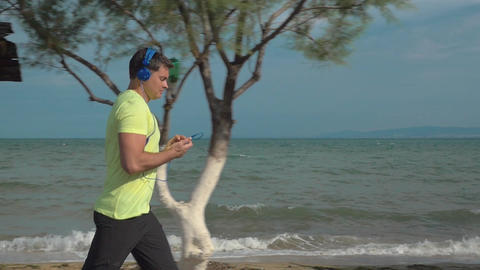 Jogging with music and smartphone at the seaside Footage