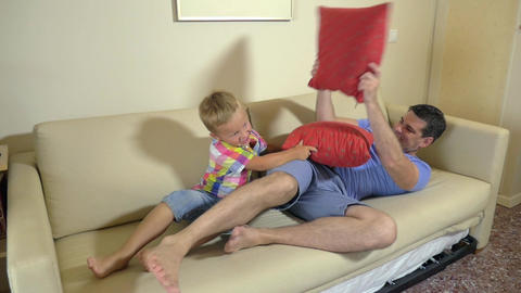 Dad and son fighting with cushions Footage