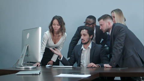 Group of multiracial business people around the conference table looking at Footage