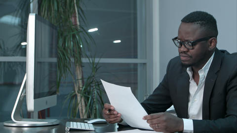 African Businessman doing paper work, calculating finance bills in office Live Action