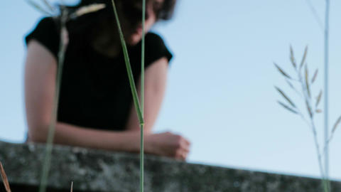 A view of a green stems, behind which is a sorrowful girl, leaning against the Footage