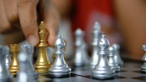 Close up shot hands of woman playing golden and silver chess select focus shallow depth of field Live Action