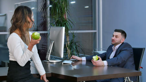 Two office workers having a break, aeting green apples and talking in office Footage