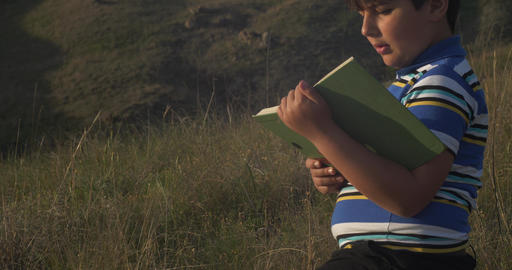 Little boy reading book He is sit on stone GIF