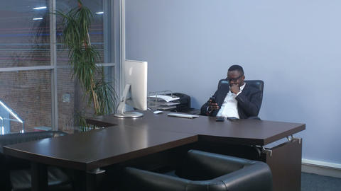 Young afro american businessman browsing with smartphone, sitting in office Footage