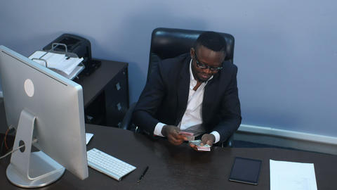 Afro-american businessman counts money, sitting in office Footage
