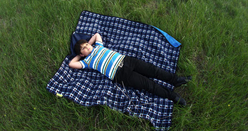 Embarrassed boy lies on a rug in the middle of a lawn with green grass and looks Footage
