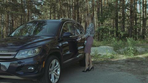 Elegant beautiful woman getting into luxury car Footage