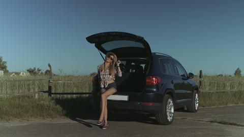 Elegant woman posing near car in countryside Footage