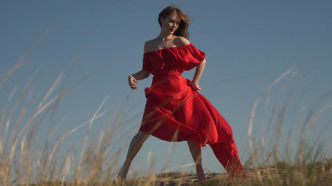 young woman model in scarlet flowing in the wind dress and barefoot at sunset Live Action