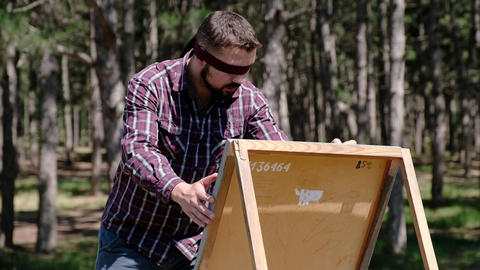 A blondfolded man enthusiastically makes sketches on a canvas while being in the Live Action