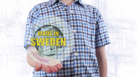 Young man shows a hologram of the planet Earth and text Made in Sweden Footage