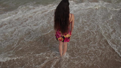 barefooted young woman standing in the surf Footage