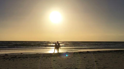 Young couple walking along the beach silhouetted against the setting sun, Footage