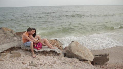 a pair of lovers sit embracing on the beach Live Action