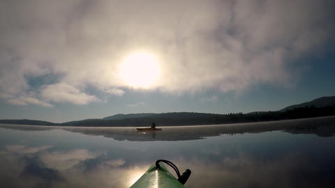 POV of a kayak tip approaching and floating another kayaker on a calm mountain Footage