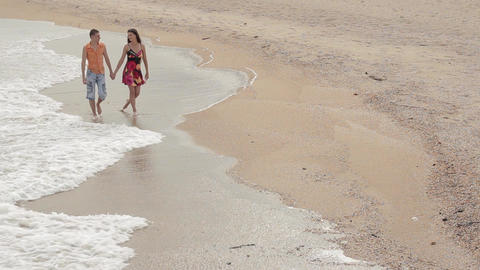 a pair of lovers walking along the sand in the surf line GIF
