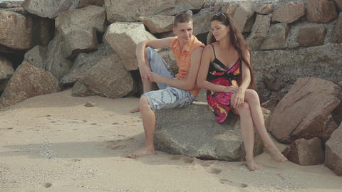 young man and woman sitting barefoot on the stone Live Action