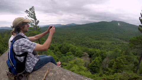Male hiker filming the view with his cell phone at the edge of a mountain cliff GIF