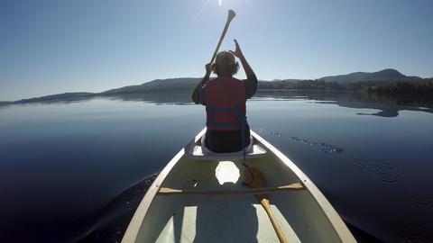 Man paddling a canoe on a tranquil placid mountain lake during the day Footage