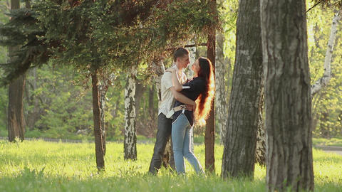 young lovers hug in the park in the sun Live Action