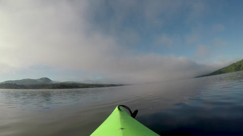 POV of the tip of a kayak drifting or floating in a calm mountain lake or river GIF