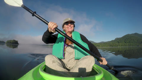 Happy smiling woman in her 40s or 50s paddling a kayak in a mountain lake having Footage