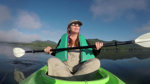 Attractive woman in her 40s or 50s resting in a kayak enjoying the view of the GIF
