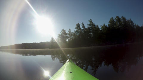 The front of a kayak floating on a mountain lake with sun glare GIF