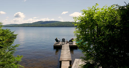 Two people relaxing on a wooden dock sitting in chairs overlooking a mountain Footage