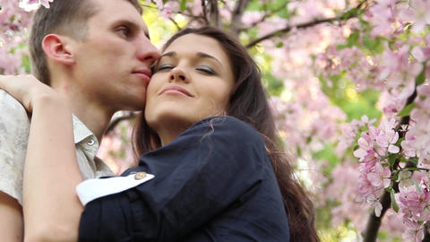 young couple in love embraces in branches of flowering tree Footage