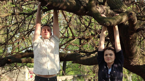 young man and woman are hanging on a tree with hands on a branch Archivo