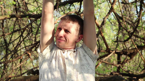 a young man hanging on a tree holding his hands behind a branch GIF
