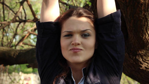 face of a young woman who smiles with her arms raised Stock Video Footage