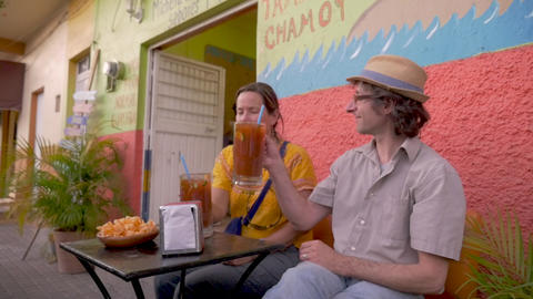 Man and woman sitting outside at a table cheering with large glass mugs of Footage