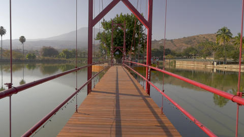 Camera walks across a calm lake or pond over a wooden suspension bridge Footage