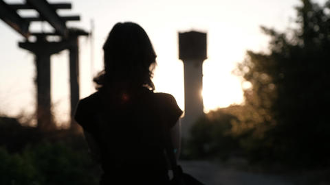 An unfocused silhouette of a young woman, walking away into the sunset Footage