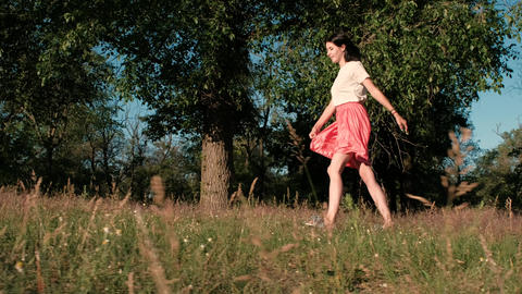 A young beautiful woman walks happily in the woods, touching her dress, hopping Footage