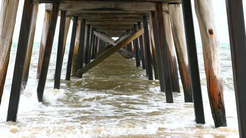4k Splashing waves at high tide under a jetty pier, taken at Grange Jetty, South Footage