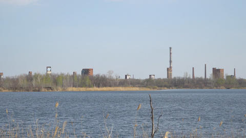 Old Abandoned chemical factory with chimneys on the banks of river ビデオ