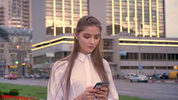 Young beautiful serious girl is typing message on her smartphone at sunset in Footage