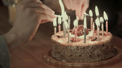 Two people lighting the candels on a birthday cake Live Action