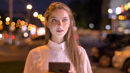 Young sweet girl is typing message on her tablet in evening in summer, thinking Footage