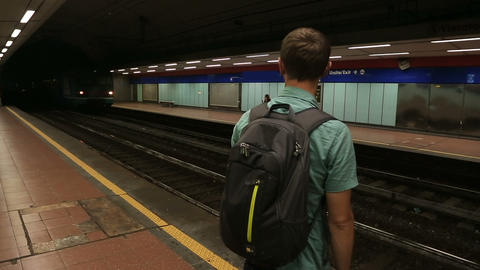 Man standing on subway platform, train passing station, public transportation Footage