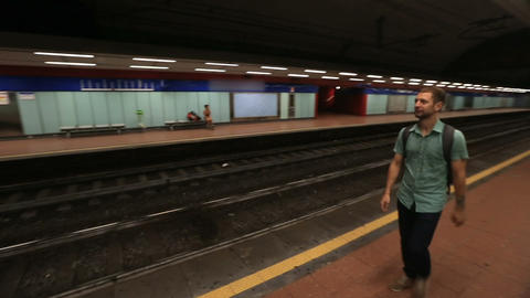 Guy standing on empty platform in underground and waiting for a train to arrive Footage